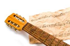 Guitare avec des notes sur un fond blanc Photographie stock