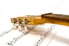 Guitare avec des notes sur un fond blanc Photos stock