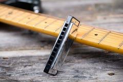 Guitare avec l'harmonica de bleus sur la terre en bois Photographie stock