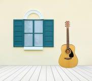 Guitare avec la fenêtre sur le mur de ciment Photo stock