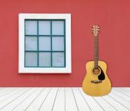 Guitare avec la fenêtre sur le mur de ciment Image libre de droits