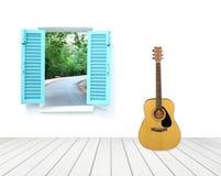 Guitare avec la fenêtre sur le mur et le plancher de ciment Image libre de droits