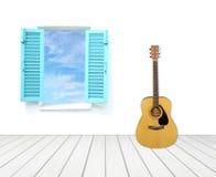 Guitare avec la fenêtre sur le mur et le plancher de ciment Photos stock