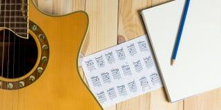 Guitare avec le carnet vide pour l'écriture de chanson Photographie stock libre de droits