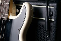 Guitare basse électrique noire et blanche avec le câble de cric et l'amplificateur classique Photographie stock