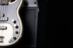 Guitare basse électrique noire et blanche avec le câble de cric et l'amplificateur classique Photo stock