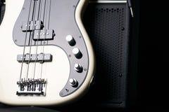 Guitare basse électrique noire et blanche avec le câble de cric et l'amplificateur classique sur un fond foncé Image libre de droits