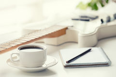 Guitare, café, bloc-notes et crayon Photo stock