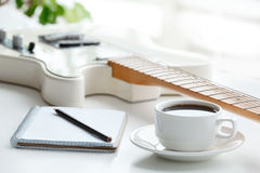 Guitare, café, bloc-notes et crayon Image stock