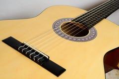 Guitare classique de corps avec la plate-forme jaune d'isolement sur le fond blanc Photos libres de droits