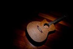 Guitare d'acajou acoustique sous un projecteur, en bas à droite de cadre Photo libre de droits