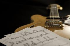 Guitare d'archtop de cru dans la vue courbe en gros plan d'érable naturel avec des feuilles de musique sur le fond noir photos stock