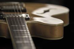 Guitare d'archtop de cru dans la vue courbe en gros plan d'?rable naturel sur le fond, les frettes et les veines noirs du d?tail  photos libres de droits