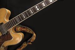Guitare d'archtop de cru en plan rapproch? naturel d'?rable avec la courroie color?e en haut dessus du fond noir photos libres de droits