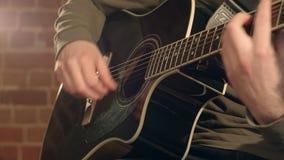 Guitare dans des mains masculines banque de vidéos