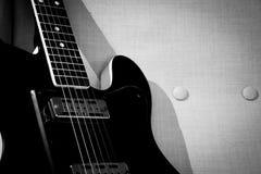 Guitare de cru sur une chaise de bras de cru photographie stock libre de droits