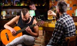 Guitare de jeu d'homme dans la barre Relaxation de vendredi dans la barre Amis détendant dans la barre ou le bar Barbus brutaux d photos stock
