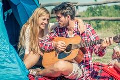 Guitare de jeu de couples dans un terrain de camping Image stock