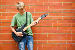 Guitare de jeu de l'adolescence Photographie stock