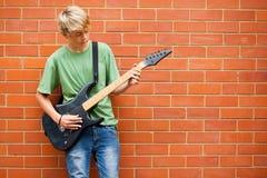 Guitare de jeu de l'adolescence Photographie stock