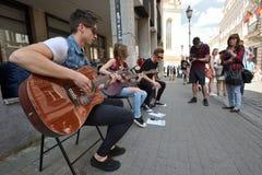 Guitare de jeu de musicien dans le jour de musique de rue Images stock