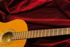 Guitare en nylon classique se trouvant sur le textile rouge de velours, présentation artistique d'instrument Images libres de droits
