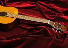 Guitare en nylon classique se trouvant sur le textile rouge de velours, présentation artistique d'instrument Photo libre de droits
