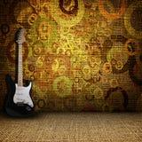 Guitare en un cuarto de la materia textil del grunge Fotos de archivo libres de regalías