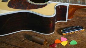 Guitare et Hamonica d'Acousitc sur la table Photo stock