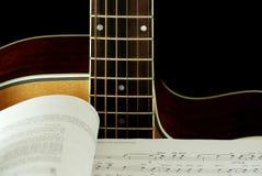 Guitare et livre avec des notes Photos stock