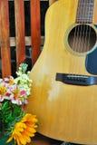 Guitare et plan rapproché de fond de fleurs Photos stock