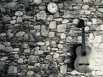 guitare, horloge, mur en pierre Images stock