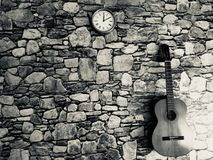 guitare, horloge, mur en pierre noir et blanc image libre de droits