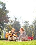 Guitare jouante supérieure à son épouse en parc Photo libre de droits