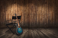 Guitare près de chaise sur le fond en bois de mur Photographie stock