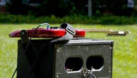 Guitare sur l'ampère dans l'herbe Photos stock