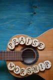 Guitare sur le bois avec des mots : ÉLOGE et CULTE Images libres de droits