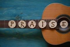 Guitare sur le bois de sarcelle d'hiver avec le mot : ÉLOGE Images stock