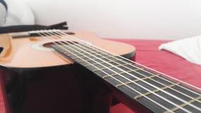 Guitare sur une feuille rouge Images stock