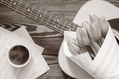 Guitare, tulipes jaunes, tasse de café, page musicale Photographie stock libre de droits