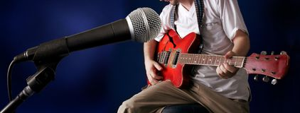 Guitarist. The figure of guitarman and microphone at front Royalty Free Stock Photography