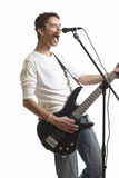 The guitarist. The young guy with a bass guitar sings in a microphone on a white background Stock Image
