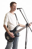 The guitarist. The young guy with a bass guitar sings in a microphone on a white background Stock Images