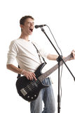 The guitarist. The young guy with a bass guitar sings in a microphone on a white background royalty free stock images