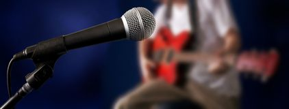 Guitarist. The blurry figure of guitarman and microphone at front Royalty Free Stock Photo