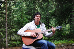 Guitarist. Man playing a guitar in the woods Stock Photography