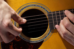 Guitarist. Acoustic guitarist playing guitar close up on fretboard and soundhole Royalty Free Stock Photo