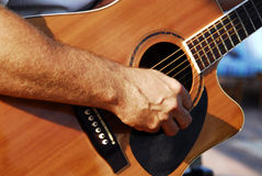 Guitarist. A closeup of a guitarist's hand, as he plucks the strings on his instrument Stock Photography