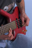 Guitarist. Close up of hands playing bass guitar Stock Images