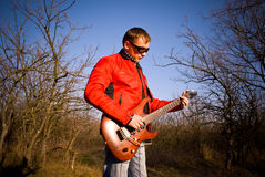 Guitarist. Plays electric guitar outdoor Royalty Free Stock Image